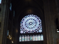 Stained_glass_window,_with_votive_lights_for_prayers,_Notre_Dame,_Paris,_ZM_